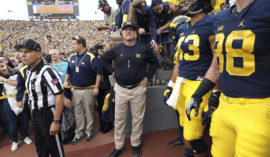 FILE - In this Oct. 1, 2016, file photo, Michigan coach Jim Harbaugh, center, waits to take the field with his players before an NCAA college football game against Wisconsin at Michigan Stadium in Ann Arbor, Mich. Michigan faces Maryland on Saturday. (AP Photo/Tony Ding, File)