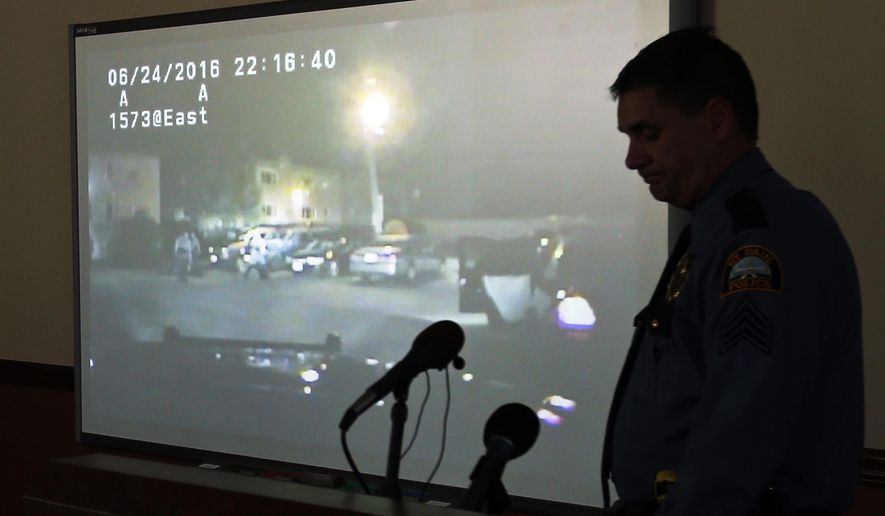 Police Sgt. Mike Ernster is silhouetted as a video is played before St. Paul Police Chief Todd Axtell addressed the media during a news conference Friday, Nov. 4, 2016 in St. Paul, Minn. Two police officers in Minnesota have been disciplined for a June incident in which a black man was kicked by an officer and bitten by a police dog, St. Paul's police chief said Friday as he released video of the confrontation. (AP Photo/Jim Mone)