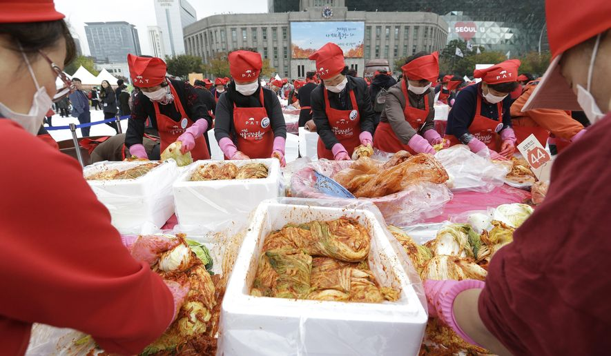 South Koreans and tourists make kimchi, a traditional pungent vegetable, to donate to needy neighbors for winter preparations during the Seoul kimchi festival in Seoul, South Korea, Friday, Nov. 4, 2016. Kimchi made with cabbage, other vegetables and chili sauce and kimchi is the most popular traditional food in Korea. (AP Photo/Ahn Young-joon).