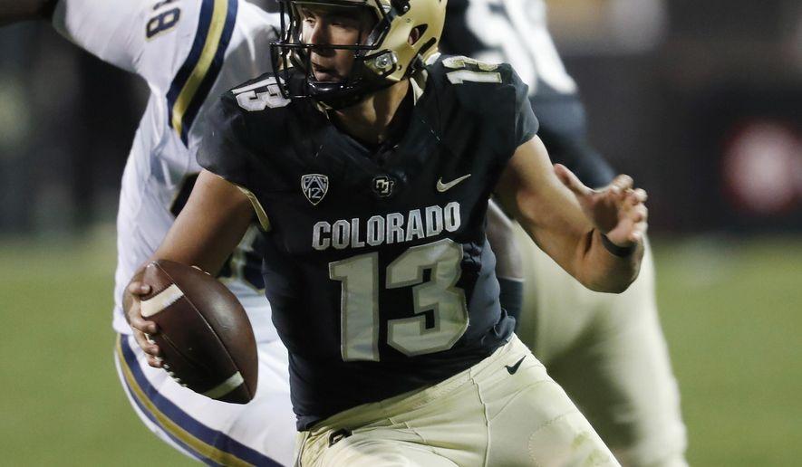 Colorado quarterback Sefo Liufau, front, evades a sack by UCLA defensive lineman Takkarist McKinley in the second half of an NCAA college football game Thursday, Nov. 3, 2016, in Boulder, Colo. Colorado won 20-10. (AP Photo/David Zalubowski)