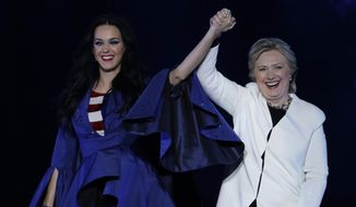 Katy Perry, left, holds the hand of Democratic presidential candidate, Hillary Clinton, right, during a concert at the Mann Center for the Performing Arts, Saturday, Nov. 5, 2016, in Philadelphia. (AP Photo/Julio Cortez)