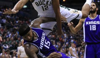 Milwaukee Bucks forward Jabari Parker, top, is fouled by Sacramento Kings center DeMarcus Cousins, bottom, during the second half of an NBA basketball game Saturday, Nov. 5, 2016, in Milwaukee. (AP Photo/Darren Hauck)