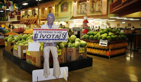"""A sign in Spanish which translates, """"Don't Lose Your Voice, Vote!"""" is displayed near a polling place in a Cardenas supermarket in Las Vegas on June 10, 2016. (Associated Press) **FILE**"""