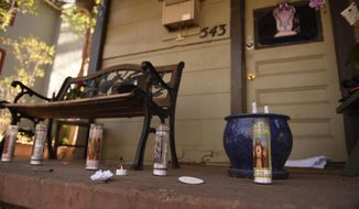 ADVANCE FOR SATURDAY, NOV. 5 - FILE - In this Nov. 2, 2015, file photo, memorial candles burn on the front porch of the Alano House on East Platte Ave. in Colorado Springs, Colo. The candles burned as a memorial to victims who died there in the Halloween Day shootings in 2015. Noah Harpham killed three people before being shot and killed by Colorado Springs police. (Mark Reis/The Gazette via AP)