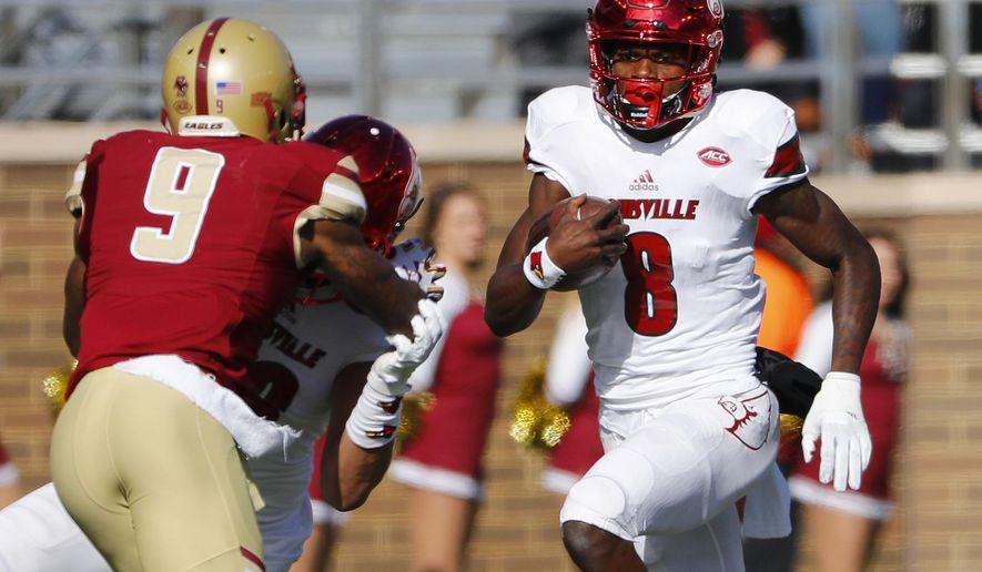 Louisville quarterback Lamar Jackson looks to run past Boston College defensive back John Johnson (9) during the first half of an NCAA football game at Alumni Stadium in Boston. Saturday, Nov. 5, 2016. (AP Photo/Winslow Townson)