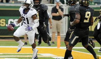 TCU running back Kyle Hicks (21) scores a touchdown on a running play after getting past Baylor cornerback Jameson Houston, rear, and cornerback Ryan Reid (9) in the first half of an NCAA college football game, Saturday, Nov. 5, 2016, in Waco, Texas. (AP Photo/Tony Gutierrez)