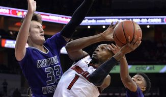 FILE - In this Nov. 3, 2016, file photo, Louisville's Tony Hicks (1) attempts to shoot through the defense of Kentucky Wesleyan's Josh Derksen (33) and Jordan Jacks during the second half of an NCAA college basketball exhibition game, in Louisville Ky. The various levels of basketball have a wide range of differing rules, from how time is kept to the distance of the 3-point arc. A handful of college coaches would like to change that so the game has uniform rules across the sport. (AP Photo/Timothy D. Easley, File)