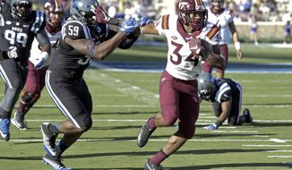 Duke's James Hornbuckle (59) chases Virginia Tech's Travon McMillian (34) as McMillian rushes for a touchdown during the first half of an NCAA college football game in Durham, N.C., Saturday, Nov. 5, 2016. (AP Photo/Gerry Broome)