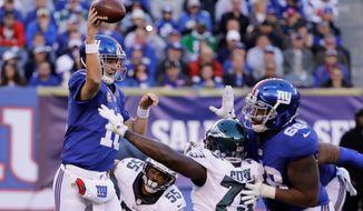 New York Giants quarterback Eli Manning throws under pressure from Philadelphia Eagles defensive end Brandon Graham in a 28-23 win on Sunday. (Associated Press) **FILE**