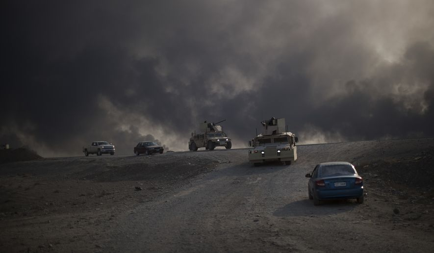Armored vehicles move Sunday toward Hamam al-Alil from Qayara, south of Mosul, Iraq. (Associated Press)