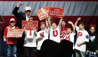 Donald Trump poses with children at a campaign rally Sunday in Sterling Heights, Michigan. (Associated Press)
