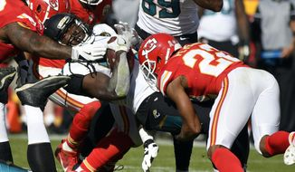 Jacksonville Jaguars running back Chris Ivory, center, is tackled by Kansas City Chiefs defensive back Marcus Peters (22) during the first half of an NFL football game in Kansas City, Mo., Sunday, Nov. 6, 2016. (AP Photo/Ed Zurga)
