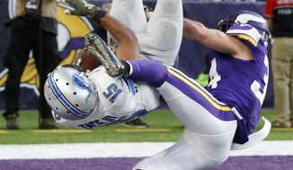 Detroit Lions wide receiver Golden Tate (15) flips into the end zone in front of Minnesota Vikings strong safety Andrew Sendejo, right, after catching a 28-yard touchdown pass during overtime in an NFL football game, Sunday, Nov. 6, 2016, in Minneapolis. The Lions won 22-16. (AP Photo/Jim Mone)