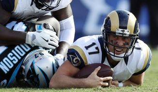 Los Angeles Rams quarterback Case Keenum, right, reacts after being sacked by Carolina Panthers defensive end Mario Addison, bottom left, during the first half of an NFL football game, Sunday, Nov. 6, 2016, in Los Angeles. (AP Photo/Ryan Kang)