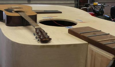 ADVANCE FOR USE SUNDAY, NOV. 6 - In this 2016 photo, a guitar rests atop a large guitar built by Sharon and Garry Wright in Fairmont, W.Va. The large guitar was built in memory of Sharon's father, Ralph Taylor and one of her favorite Sagebrush singers Rickey Whipple. The guitar was donated to the Sagebursh Round-Up — West Virginia Country Music Hall of Fame on Bunners Ridge, near Fairmont. (Kelsie VanderWijst/Times-West Virginian via AP)