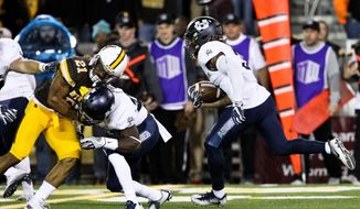 Utah State's Marquan Ellison (3) runs down the sidelines while Gerold Bright (25) tackles Wyoming's Antonio Hull (21) during the first half of an NCAA college football game in Laramie, Wyo., Saturday, Nov. 5, 2016. (AP Photo/Shannon Broderick)