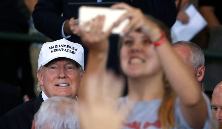 A woman takes a selfie with Republican presidential candidate Donald Trump. The increasing sophistication of digital technology can help candidates spread their message to voters but can come with pitfalls, such as Mr. Trump's oversharing on social media. (Associated Press)