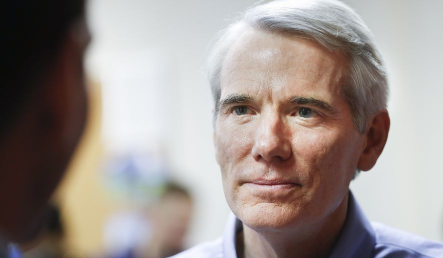 Sen. Rob Portman, R-Ohio listens to a question during a media interview at a phone bank for his reelection campaign, Monday, Nov. 7, 2016, in Columbus, Ohio. (AP Photo/John Minchillo)
