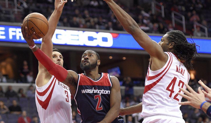 Washington Wizards guard John Wall (2) goes to the basket between Houston Rockets forward Ryan Anderson (3) and center Nene (42), of Brazil, during the second half of an NBA preseason basketball game, Monday, Nov. 7, 2016, in Washington. The Rockets won 114-106. (AP Photo/Nick Wass)