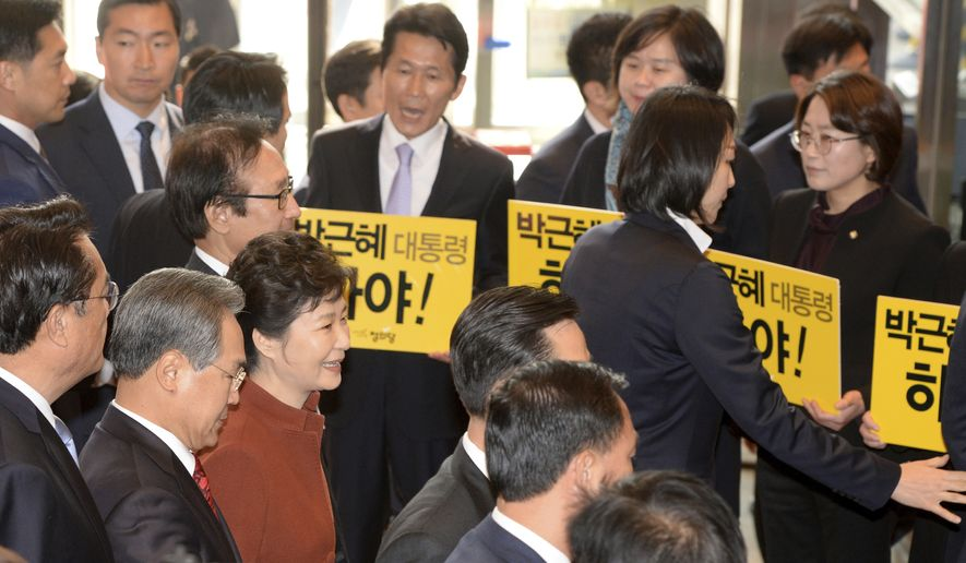 "South Korean President Park Geun-hye, third from left front, arrives as the opposition party's lawmakers holding signs reading ""President Park Geun-hye Step Down"" upon her arrival to meets with National Assembly Speaker Chung Sye-kyun at the National Assembly in Seoul, South Korea, Tuesday, Nov. 8, 2016. South Korean prosecutors have raided the Seoul office of Samsung Electronics in connection with a snowballing influence-peddling scandal involving President Park Geun-hye's longtime confidante. (Bae Jae-man/Yonhap via AP)"