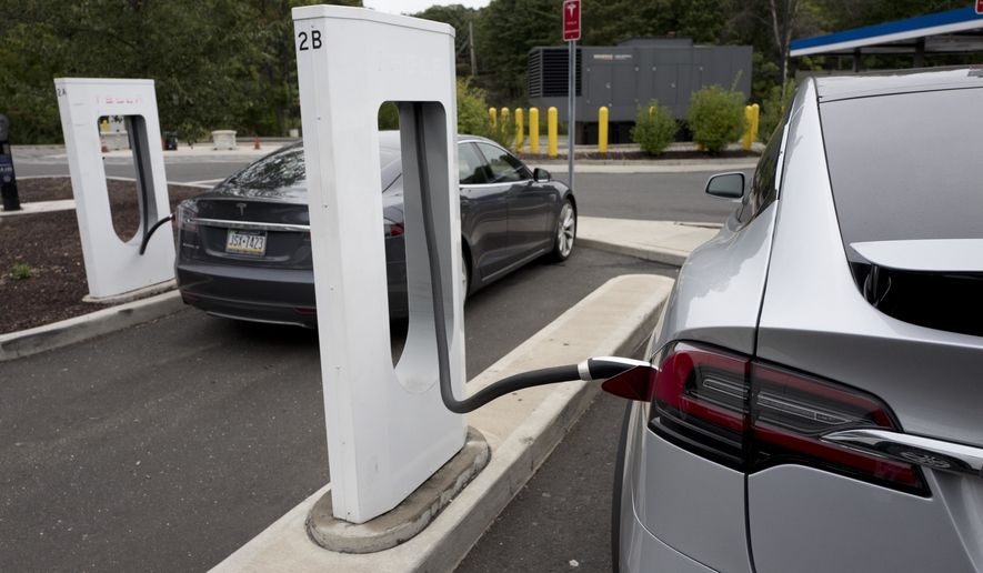 Tesla electric cars are recharged at a Tesla Motor Supercharging station at a rest stop on Interstate 95 in Darien, Conn., Sept. 18, 2016. (AP Photo/Mark Lennihan) ** FILE **