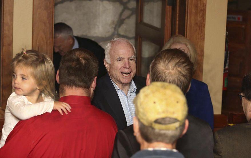 Sen. John McCain, center, greets supporters Monday, Nov. 7 2016, during a campaign stop in Flagstaff, Ariz. (Jake Bacon/Arizona Daily Sun via AP)