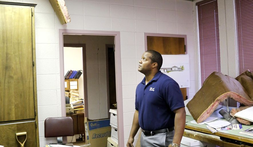Jeremy Frazier, Cushing assistant city manager, stands in his office littered with insulation, ceiling tiles and debris after Sunday night's 5.0 magnitude earthquake in Cushing, Okla. Frazier said it was a strong quake. He felt it at home which is only three blocks from city hall. (Jim Beckel The Oklahoman via AP)