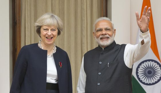 Indian prime Minister Narendra Modi, right, waves to media as his British counterpart Theresa May watches before their meeting in New Delhi, India, Monday, Nov. 7, 2016. Modi and May have begun wide-ranging talks aimed at deepening ties between their two countries and boosting trade and investment as the U.K. plans to leave the European Union. May arrived in New Delhi late Sunday on her first bilateral visit overseas since she became prime minister in July. (AP Photo/Manish Swarup)