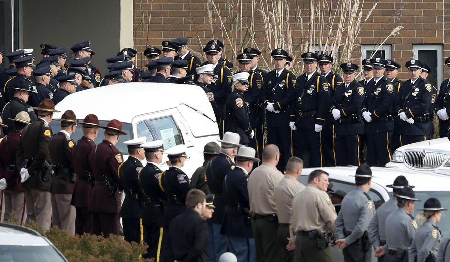 Law enforcement officers enter the Lutheran Church of Hope before funeral services for Des Moines police officer Sgt. Anthony Beminio, Monday, Nov. 7, 2016, in West Des Moines, Iowa. Beminio and Urbandale, Iowa, police officer Justin Martin were shot to death last week while sitting in their patrol cars in what authorities described as separate ambush-style attacks. (AP Photo/Charlie Neibergall)