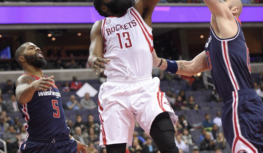 Houston Rockets guard James Harden, center, goes to the basket against Washington Wizards center Marcin Gortat, left, of Poland, and Washington Wizards forward Markieff Morris (5) during the first half of an NBA preseason basketball game, Monday, Nov. 7, 2016, in Washington. (AP Photo/Nick Wass)