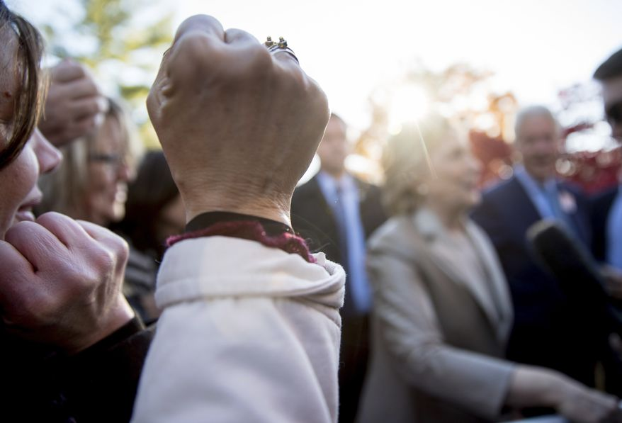 A supporter raises a fist as Democratic presidential candidate Hillary Clinton speaks to a member of the media outside Douglas G. Grafflin School in Chappaqua, N.Y., Tuesday, Nov. 8, 2016, after voting. (AP Photo/Andrew Harnik)