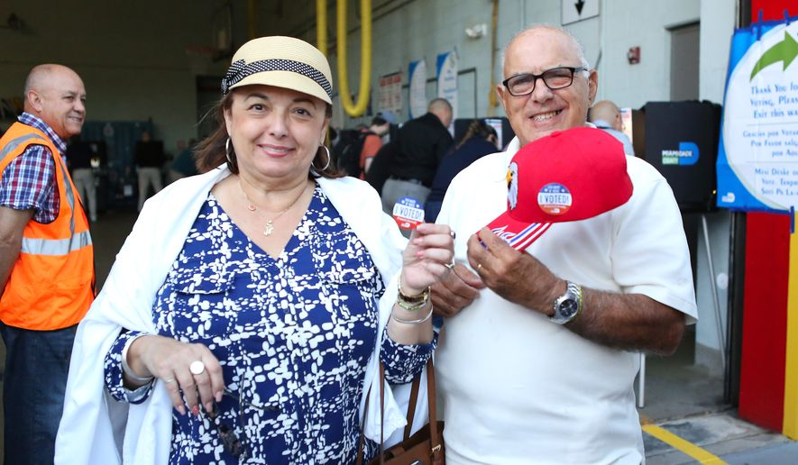 Mary and Roberto Alfonso show stickers after casting their vote in Miami-Dade County at Miami Beach Fire Station 4 on Tuesday, Nov.8, 2016. (David Santiago/El Nuevo Herald via AP)