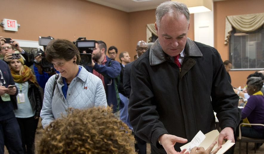 Democratic vice presidential candidate US Sen. Tim Kaine, D-Va., right, receives his ballot from a poll worker as he and his wife, Anne Holton vote in Richmond, Va., Tuesday, Nov. 8, 2016. (AP Photo/Steve Helber)