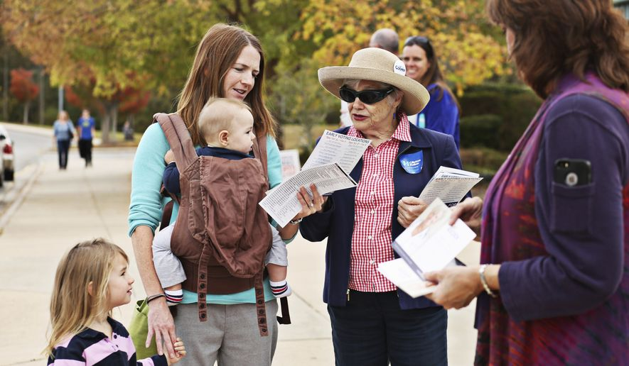 Susanne Vesilind, left, stops to speak with Democratic volunteer Maryellen Eisele, right, on her way in to Davis Drive Middle School in Cary, NC., to vote with her children, James, 5 months, and Audrey, 3, on Tuesday, Nov. 8, 2016. (Juli Leonard/The News & Observer via AP)