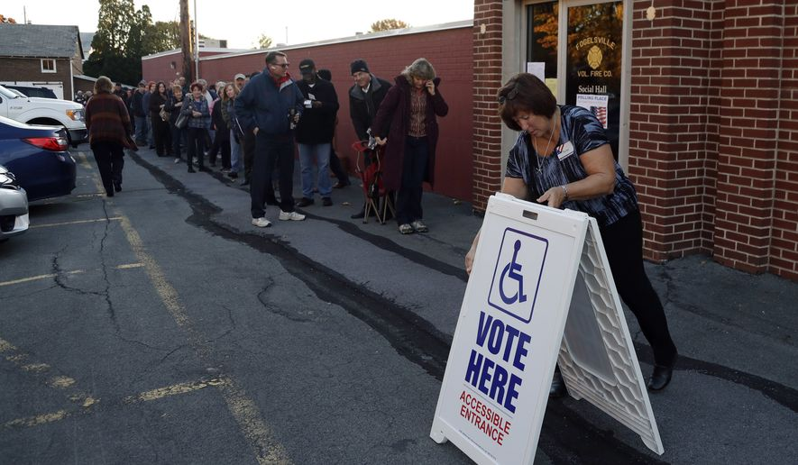 An election official places a sign as voters line up outside a polling place at the Fogelsville Volunteer Fire Co., Tuesday, Nov. 8, 2016, in Fogelsville, Pa. (AP Photo/Matt Slocum)