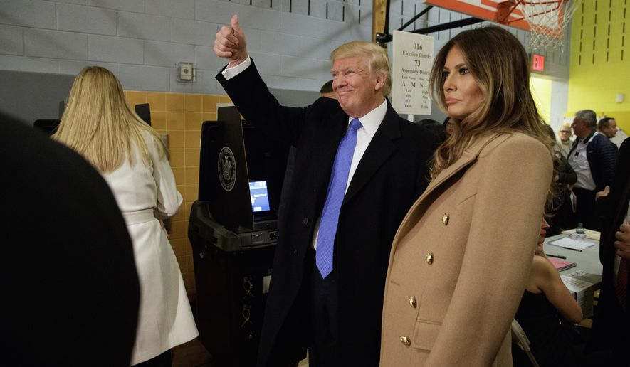 Republican presidential candidate Donald Trump, accompanied by his wife Melania. gives a thumbs-up after casting his ballot at PS-59, Tuesday, Nov. 8, 2016, in New York. (AP Photo/ Evan Vucci)