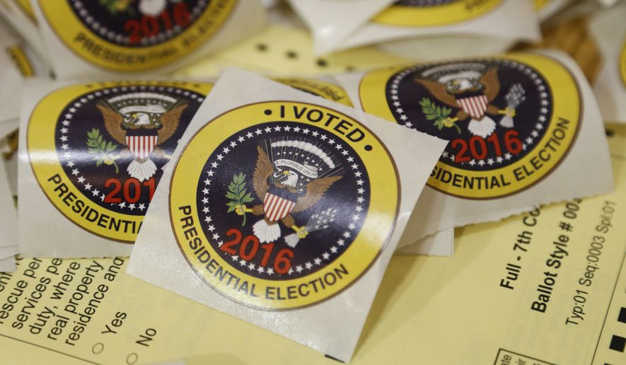 I voted stickers rest on a sample ballot ready for voters at a polling place in Richmond, Va., Tuesday, Nov. 8, 2016. (AP Photo/Steve Helber)