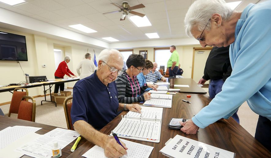 John Richard, left, checks in voters on Election Day at Jamestown Town Hall in Kieler, Wis., on Tuesday, Nov. 8, 2016. (Nicki Kohl/Telegraph Herald via AP)