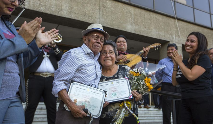 Elderly couple, Fabio Alvarado, 91 and Marta, 80 born in El Salvador, who became US citizens recently, hug as they arrive with their citizen certificates to vote for first time in Norwalk, Calif., Tuesday, Nov. 8, 2016. Fabio Alvarado was sworn in as a US citizen on Tuesday, at an Anaheim, Calif., earlier ceremony. Per California law, anyone who is naturalized after the voter registration deadline can still vote at a County Registrar office. His wife Marta became a US citizen in Sept. and registered to vote by the Oct. 24 deadline. (AP Photo/Damian Dovarganes)