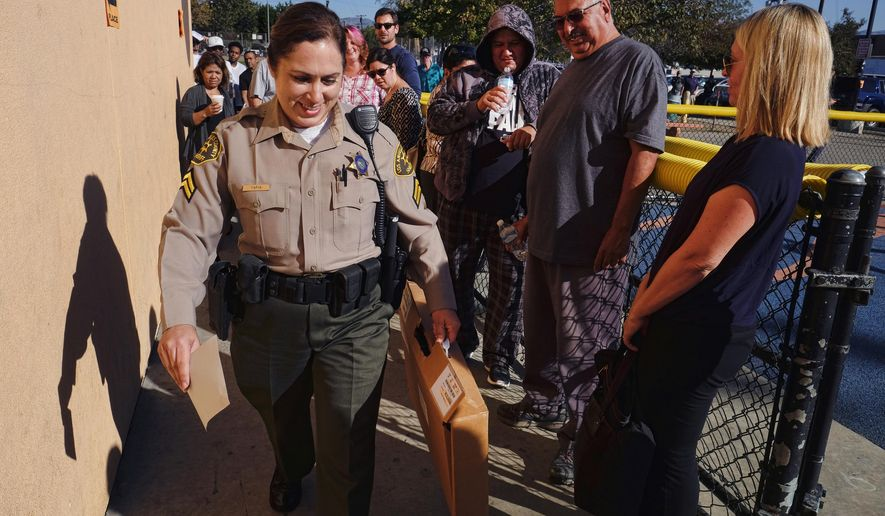 Voters who had waited hours in line to vote watch as a Los Angeles County sheriff's deputy arrives with ballot marking devices, at the Delano Recreation Center in the Van Nuys section of Los Angeles on Tuesday, Nov. 8, 2016. Frustrations ran high at the Los Angeles polling place as voters were left waiting when ballot marking devices arrived late. (AP Photo/Richard Vogel)
