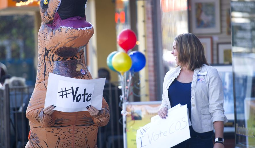 "Allison Vincent-Beckman with Citizens Project dons a dinosaur costume Tuesday, Nov. 8, 2016, to become ""Votasaurus Rex"" and encourage people in downtown Colorado Springs, Colo. to get out and vote. (Mark Reis/The Gazette via AP)"