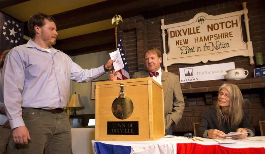 Dixville Notche's first voter Clay Smith drops his ballot into the box as moderator Tom Tillotson watches Tuesday, Nov. 8, 2016, in Dixville Notch, N.H. Democratic candidate Hillary Clinton beat Republican Donald Trump 4-2. (AP Photo/Jim Cole)