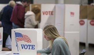 A woman votes with others at a Edmond, Okla., church Tuesday, Nov. 8, 2016. Officials at the site report that 40% of the registered voters had voted today. (AP Photo/J Pat Carter)