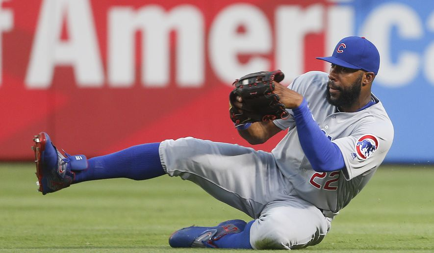 FILE - In this June 10, 2016, file photo, Chicago Cubs right fielder Jason Heyward makes a sliding catch on a fly ball by Atlanta Braves' Nick Markakis during the third inning of a baseball game Friday, June 10, 2016, in Atlanta. Heyward and Cubs first baseman Anthony Rizzo won Golf Glove awards for fielding excellence, which were announced Tuesday, Nov. 8. (AP Photo/John Bazemore, File)