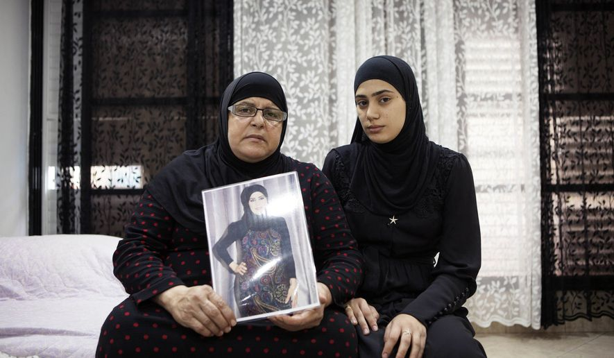 In this photo taken Thursday, Nov. 3, 2016, Israeli Arab Majeda Abu Sharkh left, holds a picture of Duaa Abu Sharkh that was killed in Lod as she poses for a photograph with her niece Alaa Khalili, in Lod, central Israel. After years of abuse and death threats, Duaa Abu-Sharkh had finally divorced her husband, agreeing even to give up custody of her four young children to escape his violent grip. Then, one night in late September, as she was dropping off her kids after a rare visitation, a masked gunman dragged her from her car in the center of this crime-ridden city and shot her in the head before their eyes.  (AP Photo/Dan Balilty)
