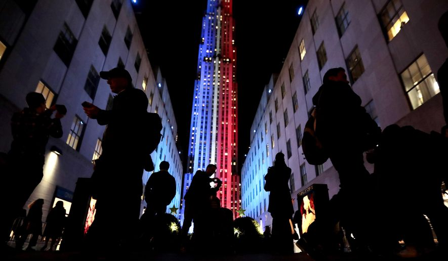 People stop for photographs in front of an Rockefeller Center, which is illuminated in patriotic lights during an Election Day gathering, Tuesday, Nov. 8, 2016, in New York. (AP Photo/Julio Cortez)