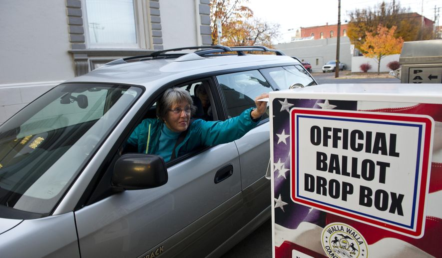 A driver drops her ballot off in an alley on South Fourth Avenue in Walla Walla, Wash., Monday, Nov. 7, 2016. (Michael Lopez/Walla Walla Union-Bulletin via AP)