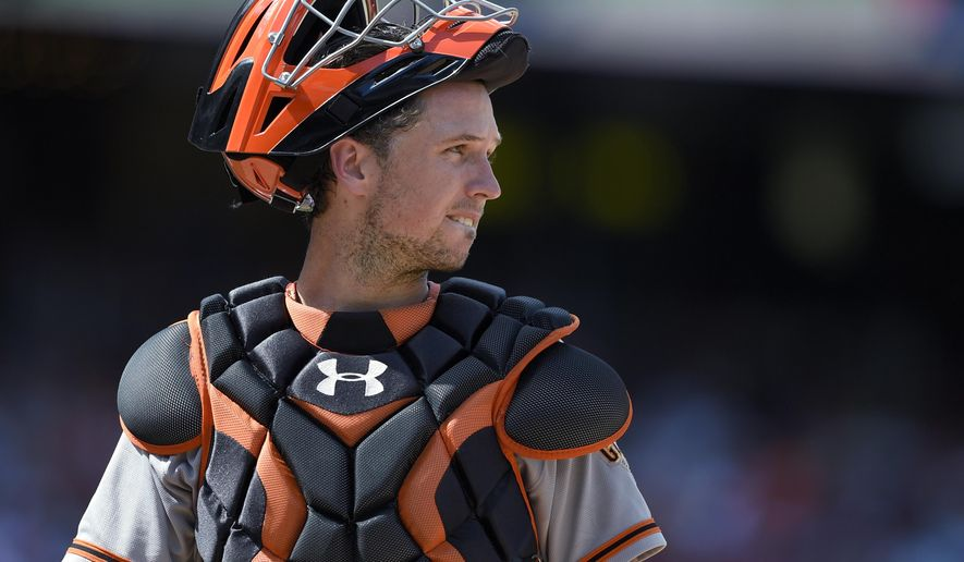 FILE - In this Aug. 7, 2016, file photo, San Francisco Giants catcher Buster Posey looks toward the infield during the team's baseball game against the Washington Nationals in Washington. Posey won a Gold Glove award for fielding excellence, announced Tuesday, Nov. 8, by Rawlings. (AP Photo/Nick Wass, File)
