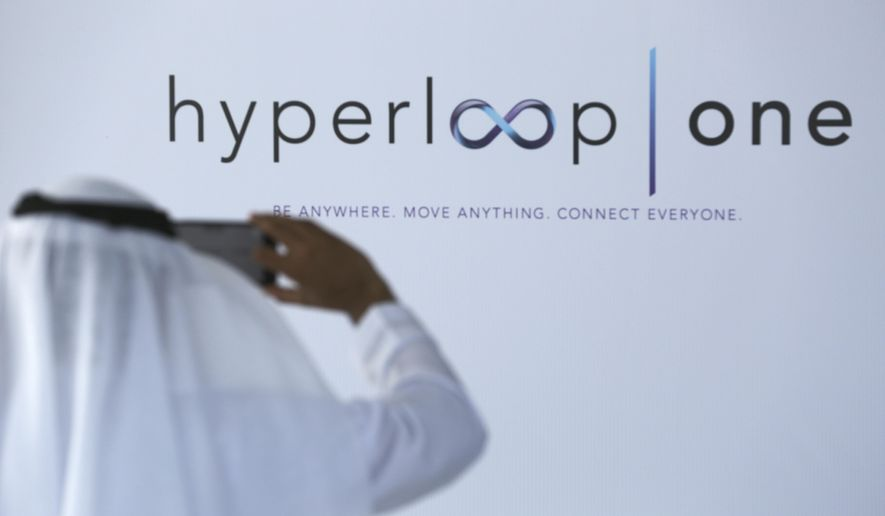 An Emirati takes a photograph of the Hyperloop One logo with his mobile phone in Dubai, United Arab Emirates, Tuesday, Nov. 8, 2016. The futuristic city-state of Dubai announced a deal on Tuesday with Los Angeles-based Hyperloop One to study the potential for building a line linking it to the Emirati capital of Abu Dhabi. (AP Photo/Jon Gambrell)
