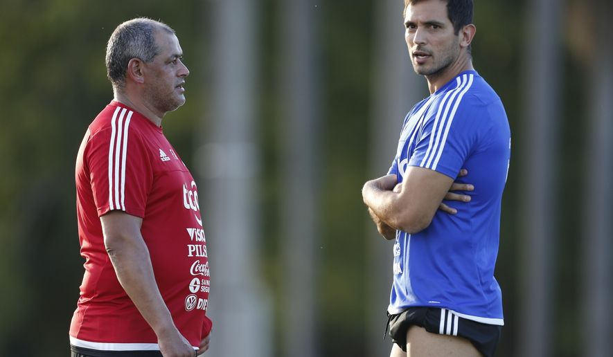 Paraguay's coach Francisco Arce, left, listens to player Roque Santa Cruz during as training session at Ypane, Paraguay, Monday, Nov. 7, 2016. Paraguay will face Peru in a 2018 World Cup qualifying match Thursday. (AP Photo/Jorge Saenz)